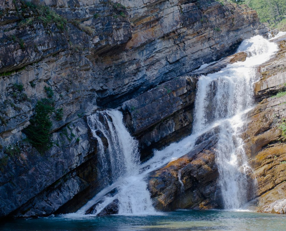 Waterfall in Waterton, slant of rock layers show direction of earth
